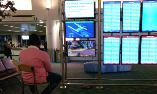 Passenger Takes Over Airport Monitor To Play Video Game